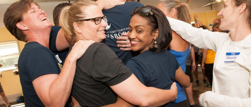 Kinesiology students hug one another.