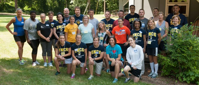 A group of students in the online EdD in Kinesiology program are gathered together outside as part of a retreat.